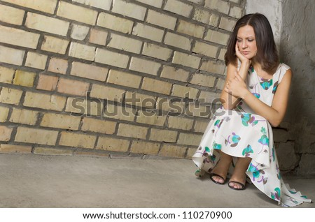 Depressed woman seeking solitude crouched low against a brick wall with her chin on her hand and downcast eyes