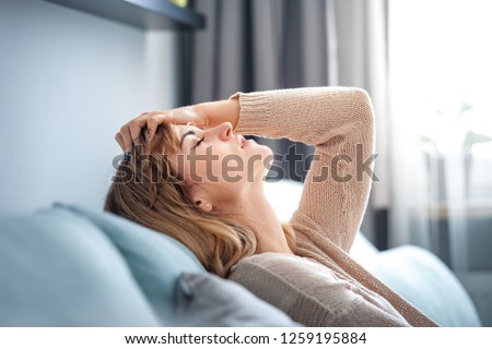 Depressed woman sitting on sofa at home, thinking about important things #1259195884