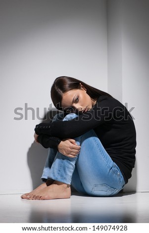 Depressed women. Young depressed women sitting on the floor and holding her head on knees