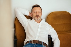 Depressed worried middle-aged man lying back in chair thinking with a sombre faraway expression and his hand behind his head