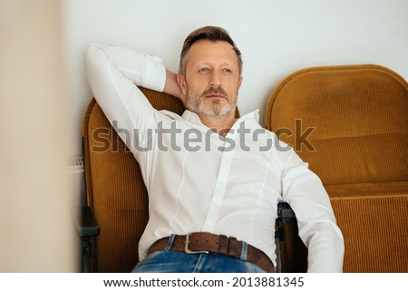 Depressed worried middle-aged man lying back in chair thinking with a sombre faraway expression and his hand behind his head Photo stock ©