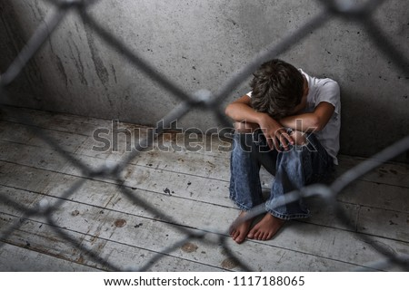Depressed young boy sitting alone behind a chain link fence