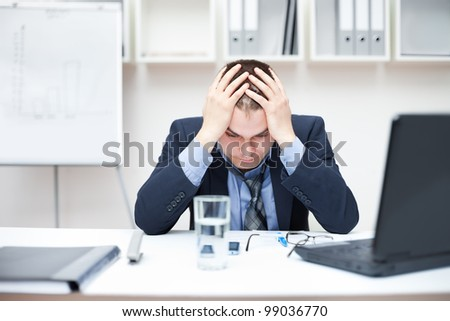 Depressed young business man holding his head at office - stock photo