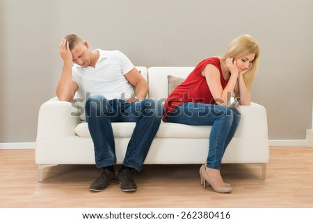 Depressed Young Couple Sitting On Sofa At Home