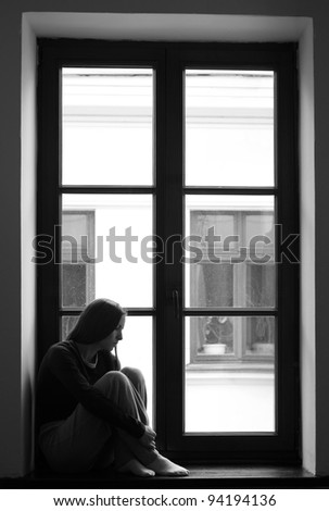 Depressed young girl sitting lonely on windowsill