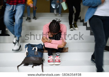 Depressed young student with face mask sitting on floor back at college or university, coronavirus concept. Photo stock ©