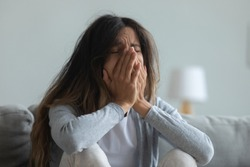 Depressed young woman crying, covering face with hands close up, suffering from break up with boyfriend or divorce with husband, bad relationship, mental psychological problem, feeling lonely and sad