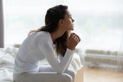 Depressed young woman feeling lonely and sad, sitting on bed in bedroom, looking in distance, thinking about problems, upset unhappy girl suffering from break up with boyfriend or divorce