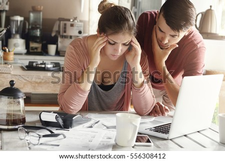 Depressed young woman having bad headache holding her temples feeling stressed by lack of money to pay out family debts, her puzzled husband standing next to her, trying to come up with solution