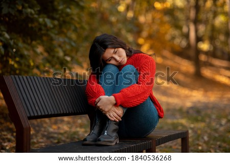 Depressed young woman hugging her knees while sitting on bench at yellow autumn park. Millennial lady feeling stressed or unhappy, suffering from loneliness or seasonal affective disorder, outdoors Photo stock ©
