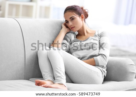 Depressed young woman on sofa at home