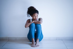 Depressed young woman sitting near concrete wall
