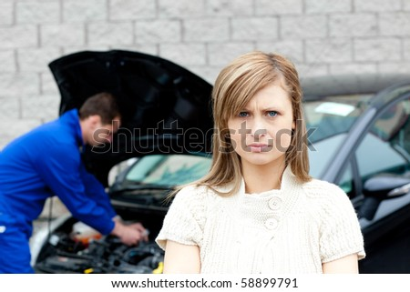 Depressed young woman standing in front of her car at the garage