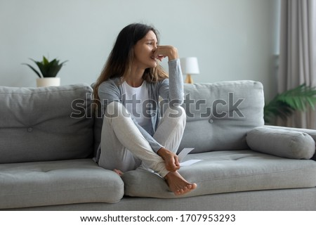 Depressed young woman suffering from break up with boyfriend or divorce with husband, holding torn photo, bad relationship, stressed upset girl crying, feeling lonely, sitting on couch at home alone