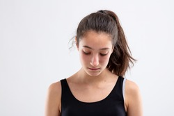 Depressed young woman with a ponytail posing looking down with a sad expression over a white studio background
