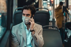 Depressing scene of a young man wearing a surgical mask during the coronavirus outbreak in Europe, talking on his mobile phone. Public transportation curfew.