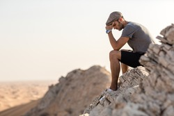 Depression and loneliness. Sad man sitting alone on top of a mountain cliff overlooking the desert.