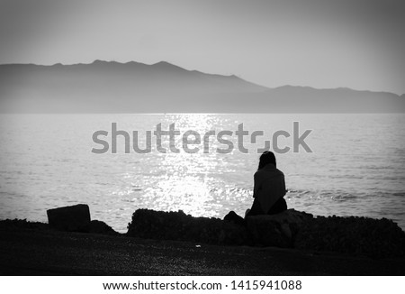 depression. black and white photo of a melancholic girl sitting alone by the sea feeling sad and contemplating