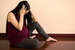 Depression during pregnancy. Stressful pregnant woman sitting on the floor. Emotional pregnant woman with copy space.