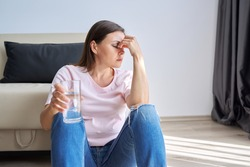 Depression, neurosis, fears, stress, mental health problems, the consequences of the disease coronavirus covid-19. Sad unhappy mature woman sitting at home on floor with glass of water