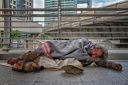 depression poor homeless man getting to sleep on floor in public path way with old hat in front for money donation