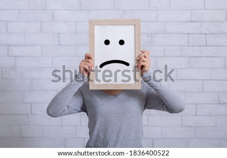 Depression, sadness, negative emotions concept. Young woman holding picture frame with sad emoticon in front of her face. Millennial lady expressing pessimism, loneliness, grief or frustration Сток-фото ©