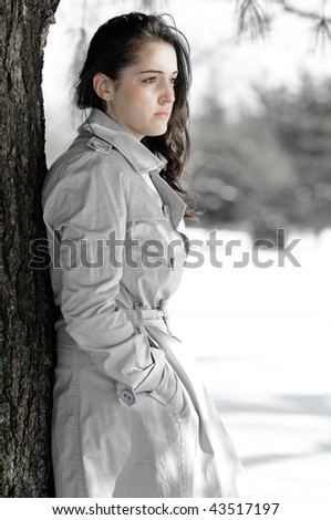 Depression series - desaturated image of young woman alone in winter scene