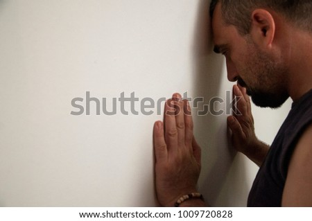 Depressive man turned to the wall with anxious and displeased feelings. Negative emotions.