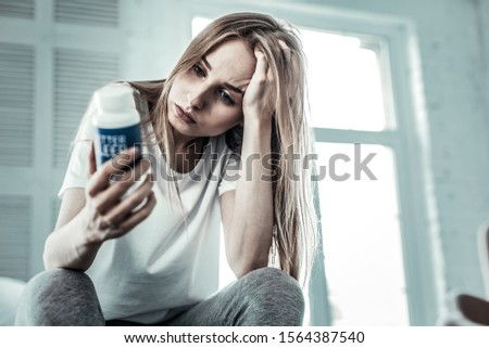 Depressive mood. Depressed young woman touching her hair while holding sleeping pills