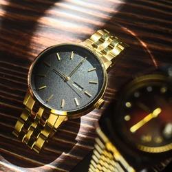 Depth close up gold watch natural sunlight on dark wood background