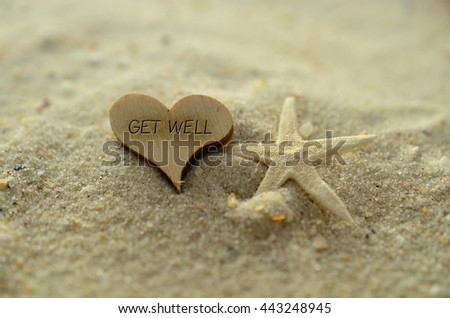 Depth of field get well text carved/engraved in heart shape piece of wood on sand beach with starfish #443248945