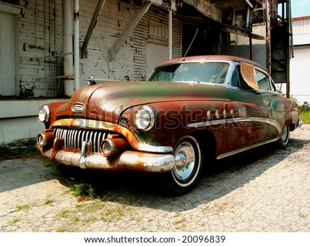 stock photo : Derelict vintage car with for sale sign in front of abandoned