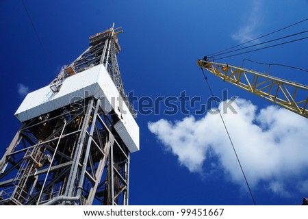 Derick of jack up drilling rig with the rig crane on sunny day