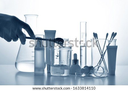 Dermatologist formulating and mixing pharmaceutical skincare, Cosmetic bottle containers and scientific glassware, Research and develop beauty product concept. Stock photo ©