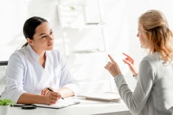 dermatologist sitting at table and listening to patient in clinic