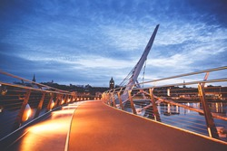 Derry, Ireland. Illuminated Peace bridge in Derry Londonderry, City of Culture, in Northern Ireland with city center at the background. Night cloudy sky with reflection in the river at the dusk.