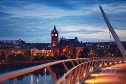 Derry, Ireland. Illuminated Peace bridge in Derry Londonderry, City of Culture, in Northern Ireland with city center at the background. Night cloudy sky with reflection in the river at the dusk