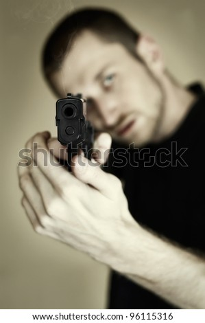 Desaturated image of a man pointing a gun at you