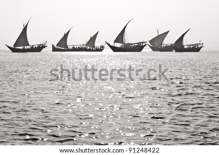 Desaturated image of Arabian dhows, performing during the Qatar National Day festivities in Doha - stock photo