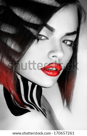 Desaturated portrait of sexy caucasian woman with red lips in studio