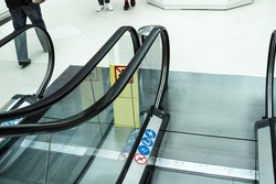 Descending the escalator in the shopping center. Railings and lower landing with pictographs
