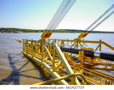 Descent of the pipeline to a bottom exhausting with the pipelaying barge. Installation of the underwater gas pipeline. Laying of pipes with pipe-laying barge crane near the shore
