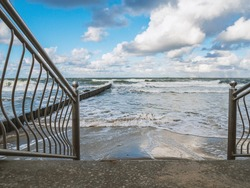 Descent to the sea by stairs in a storm. Metal fences in the foreground and breakwaters in the background.