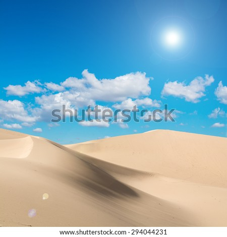 Desert and sunlight with lens flare in blue sky and clouds background