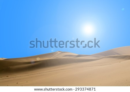 Desert and sunlight with lens flare in blue sky background