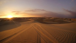Desert at sunrise sunset hour with dune buggy tires tracks in the sand in the foreground. Buggy tour in Huacachina, Ica, Peru. Extreme sports, adventure, journey and travel concept. Wide angle shot.