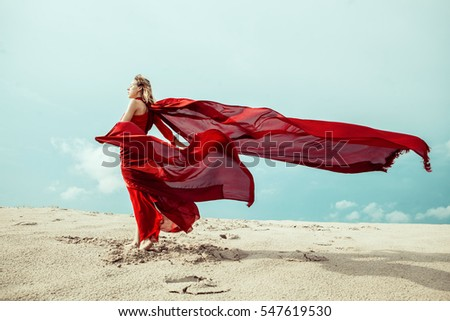 Desert dance. Beautiful model in red dress dancing in the desert. Wasteland action. Color contrast red and cyan. - Shutterstock ID 547619530
