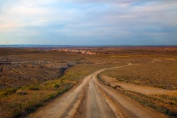 Desert, dirt road to Coalmine Canyon, near Page Arizona.  Taking looking downhill of an 8% grade.  The landscape is lit by golden light, filtered through a smoky sky.