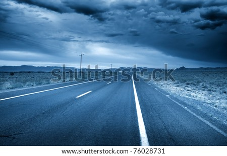 Desert drive with stormy sky in blue color