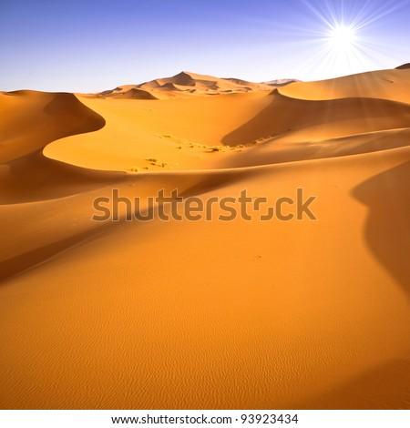 Desert dunes landscape with sun flare on blue sky background.